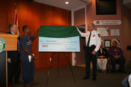Sheriff Al Lamberti presents Mark Spradley with a check for $2,500 from Broward Crime Stoppers
