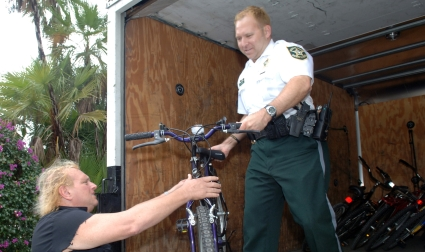 Deputy Brian Faust hands over a BSO evidence bicycle to the father of a high school student who refurbishes them for needy children.