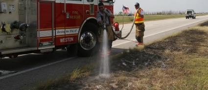 Broward Sheriff Firefighter Gonzalo Curbelo (left) and Driver/Engineer Jim Harkins douse a hot spot along U.S. 27 Monday.